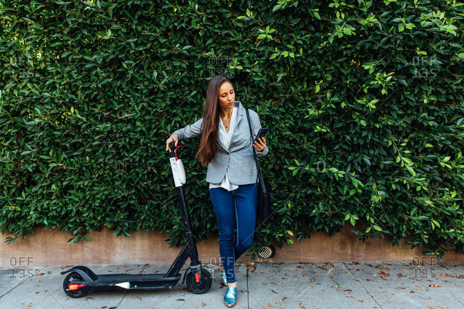 Woman looks at phone with scooter