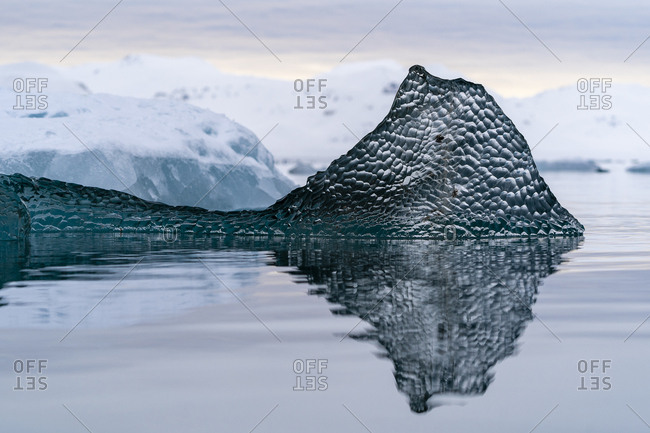 A piece of translucent ice like glass, floats on the ocean
