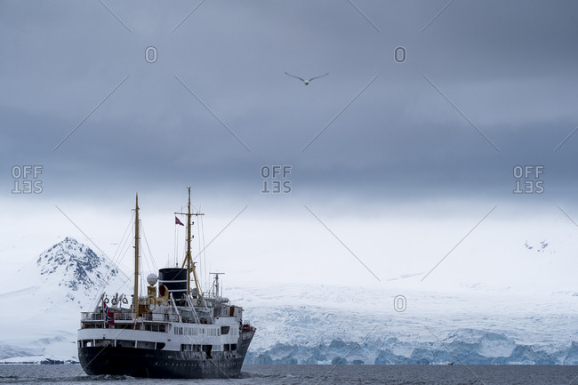 A cruise ship sails in arctic waters. a glacier in the background