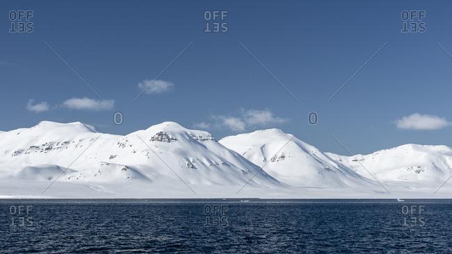 Snowy mountains of spitsbergen under a blue spring sky