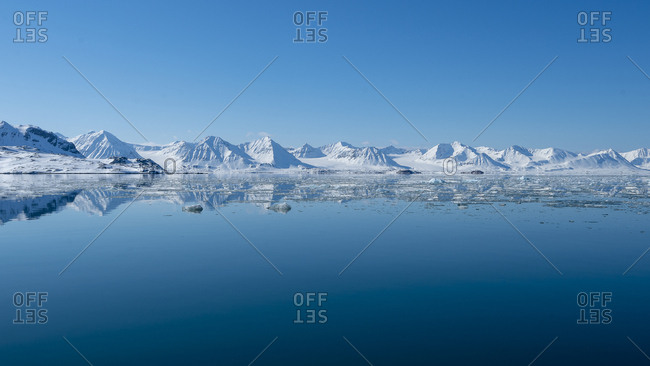 Panoramic view of snow-capped mountains that is reflected in the sea