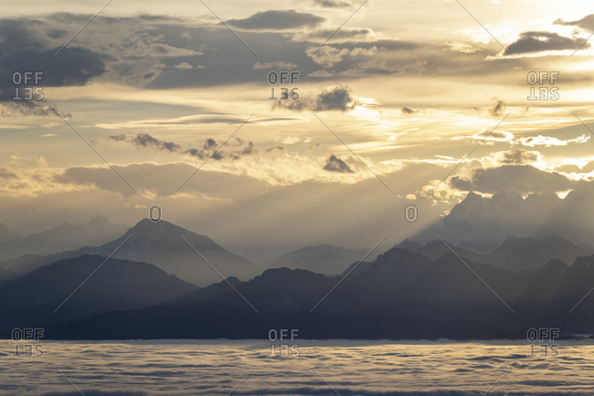 View of the alps at sunrise, in the foreground lake geneva cloudy