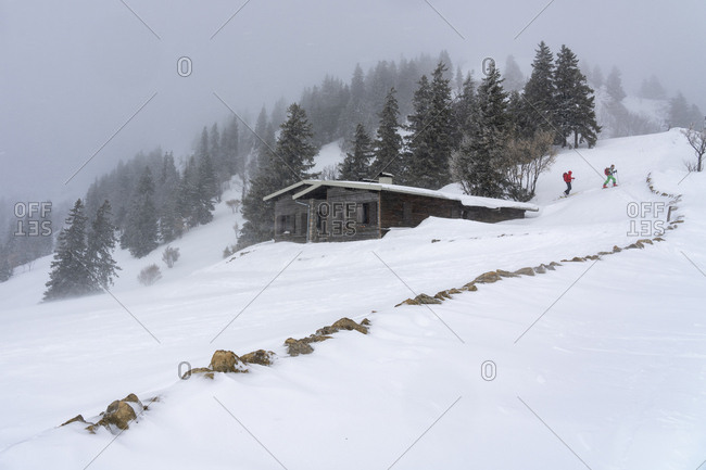 In a winter landscape, two hikers pass near a mountain chalet