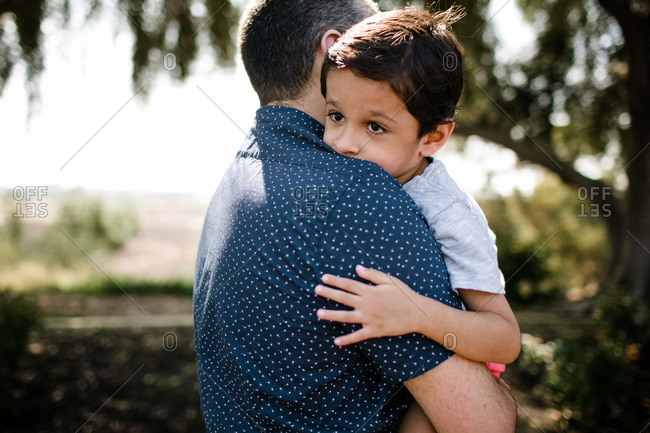 Autistic boy hugging dad while standing under tree