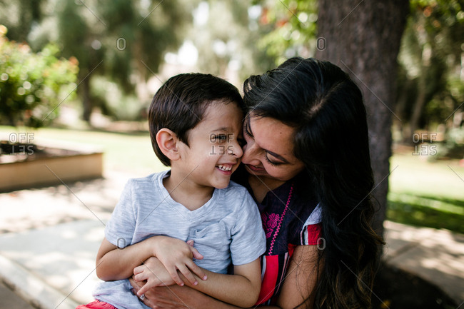 Mother & autistic son smiling & hugging under tree