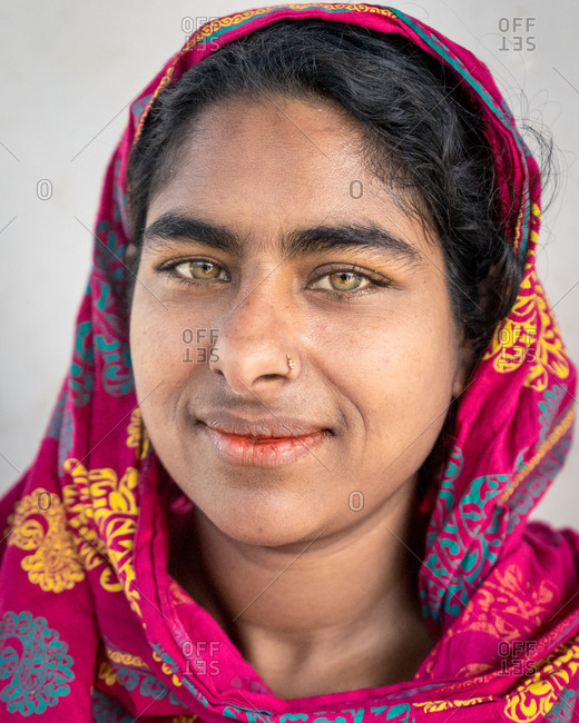 Sylhet, Bangladesh - January 27, 2019: Portrait of bangladeshi woman with green eyes and red headscarf