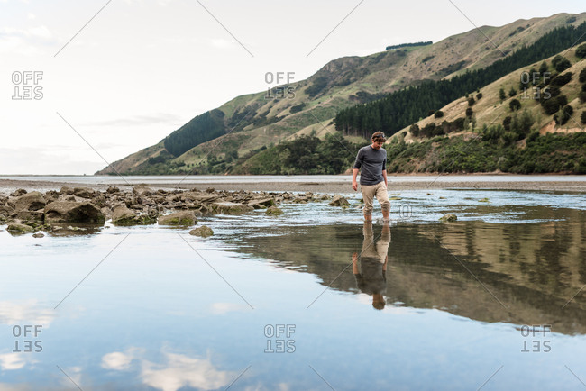 Man walking in estuary at low tide