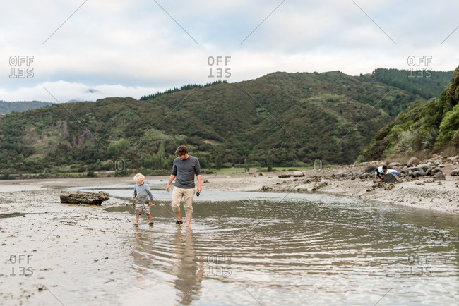 Father and young son walking in shallow water in new zealand