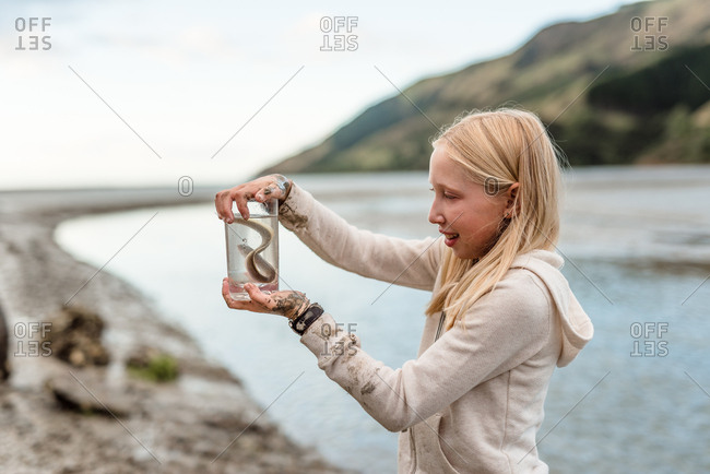 Tween girl holding an eel in new zealand
