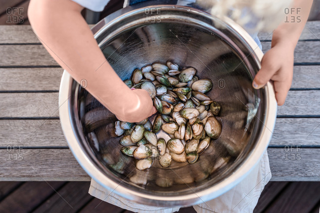 Toddler holding a large bowl of fresh shellfish
