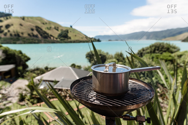 Pot with lid on a small grill with scenic view