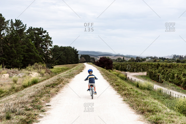 Young boy riding a bike on remote path in new zealand