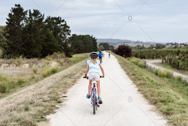 Tween girl riding a bicycle on a path in new zealand