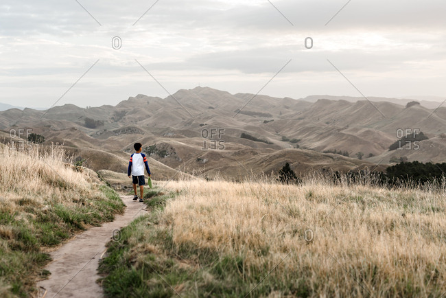Preteen boy walking on a scenic path with mountains