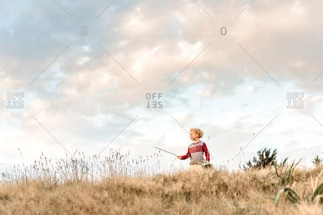 Preschooler using imagination pretending a stick is a wand
