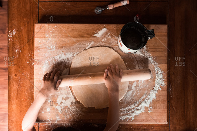 Small hands rolling pastry dough onto a wood cutting board on a table