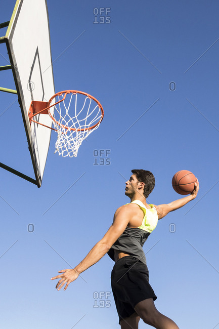 Man jumping high and throwing ball in hoop