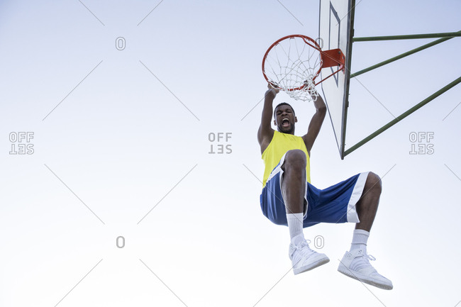 Man in sportswear hanging on hoop and shouting