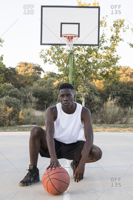 Young African man with basketball on basketball ground