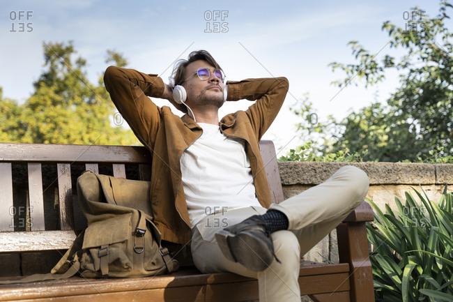 Man sitting on bench listening music with headphones