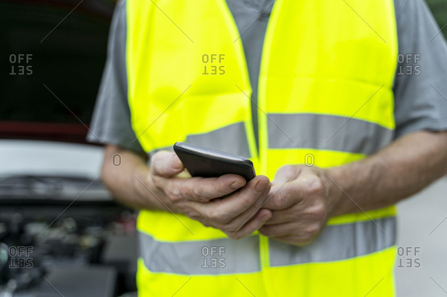 Close up of a senior man standing at his broken car wearing a safety vest and using his smartphone