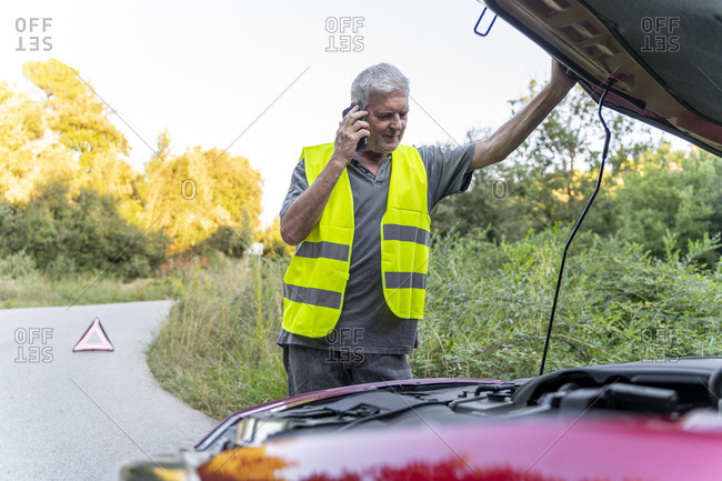 Senior man standing at his broken car wearing a safety vest and using his smartphone