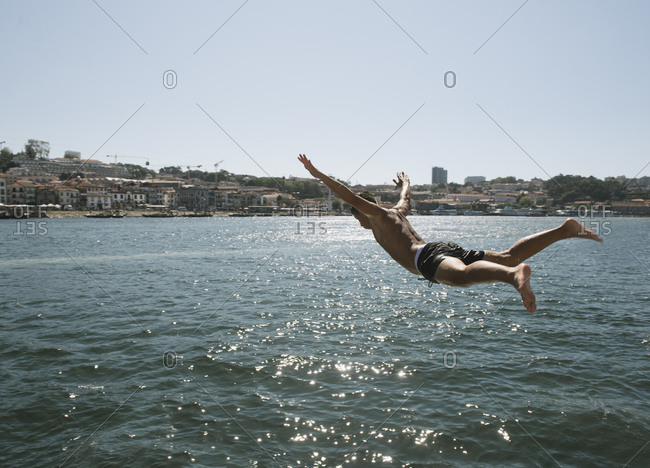 Young man jumping into the water- Porto- Portugal