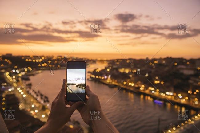 Woman's hands holding smartphone with a photo of panoramic view of Porto at sunset- Portugal