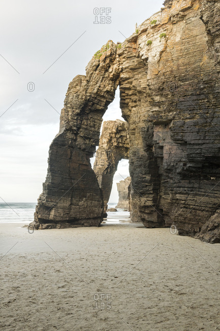 Spain- Galicia- Rock arches on Cathedrals Beach at sunset