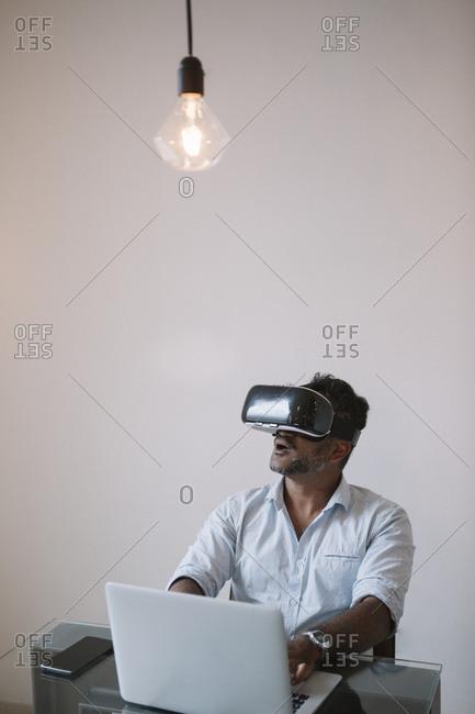 Businessman sitting at table testing VR simulator