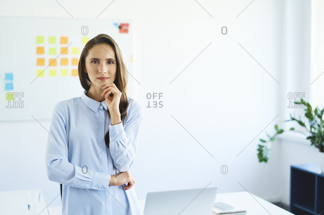 Portrait of confident young businesswoman standing in office looking at camera