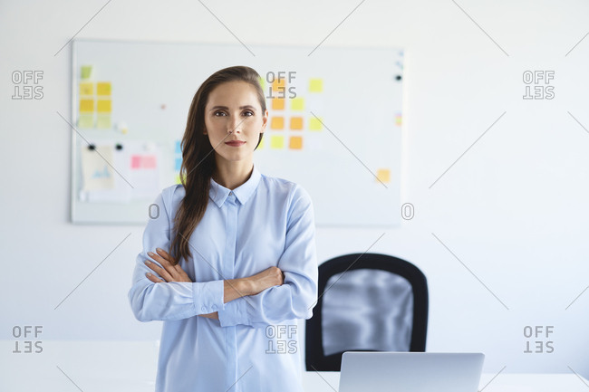 Portrait of confident businesswoman looking at camera with crossed arms in office