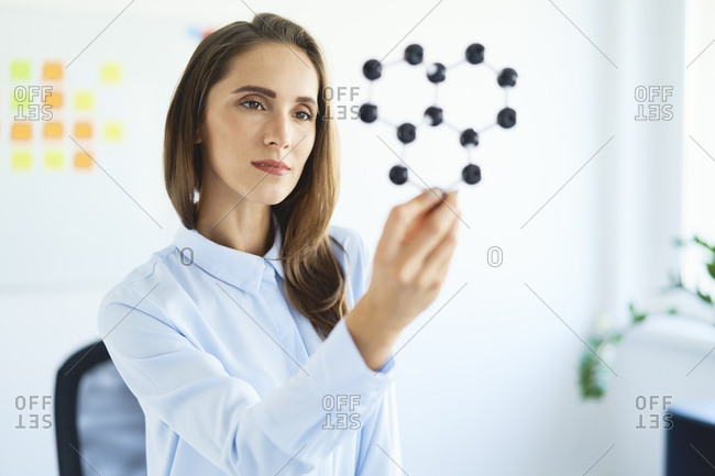Young female scientist looking at graphene model