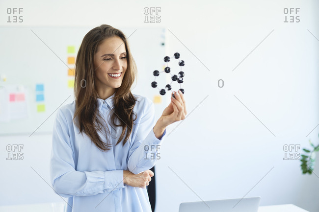 Smiling young scientist looking at graphene model in office