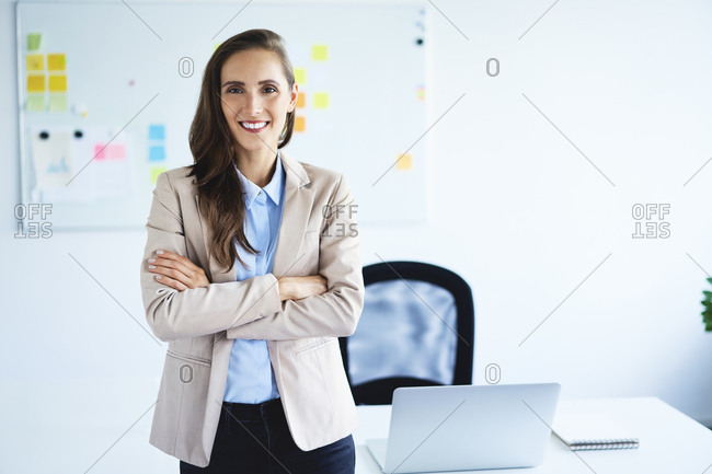 Cheerful young businesswoman looking at camera with crossed arms standing in office