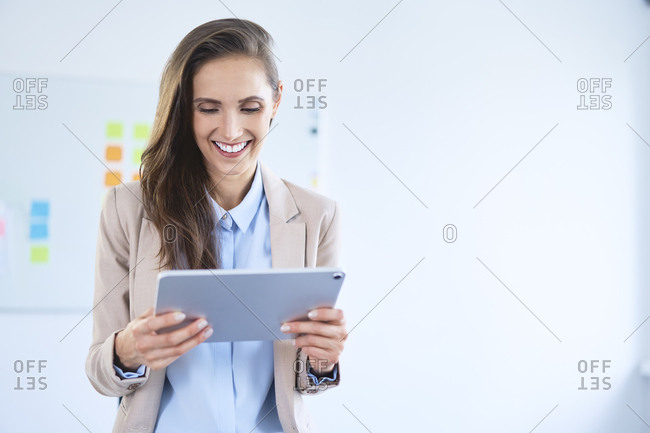 Smiling businesswoman using tablet in office