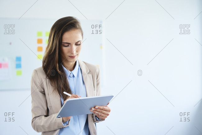 Young businesswoman writing on tablet in office
