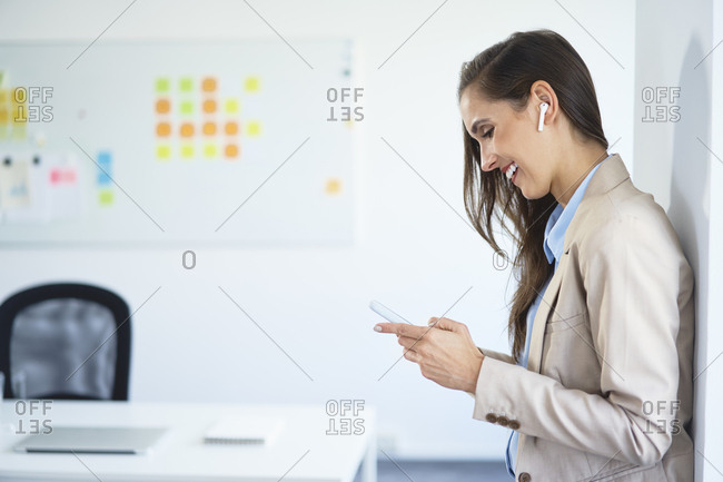 Young businesswoman standing in office using phone and wireless earphones