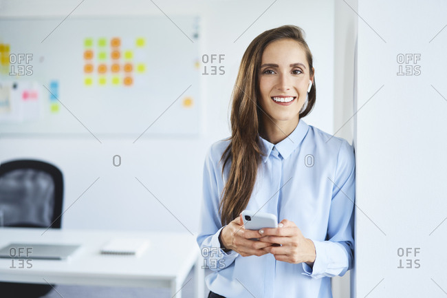 Young businesswoman with wireless earphones holding phone standing in office