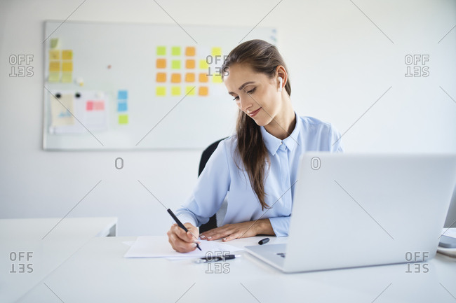 Young businesswoman preparing business documents while working with laptop in office