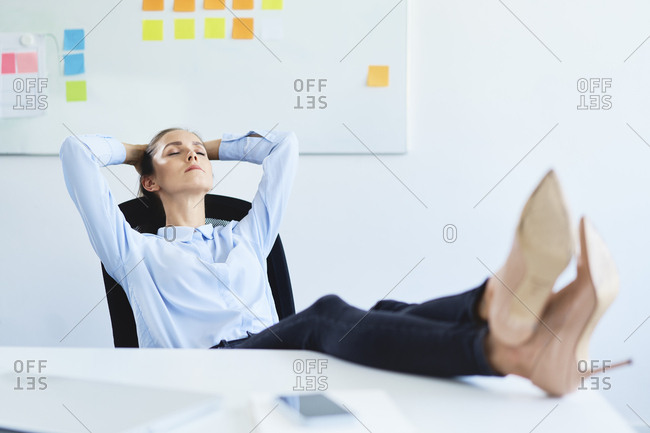 Young businesswoman relaxing in office reclining with feet on desk