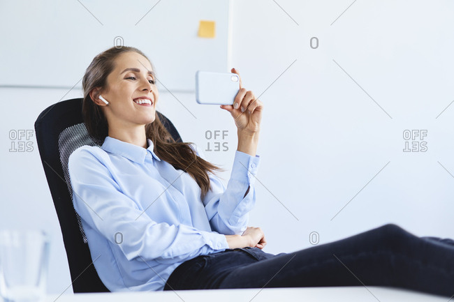 Young businesswoman sitting in office during phone video call