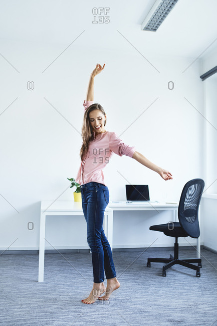 Cheerful young woman standing in office