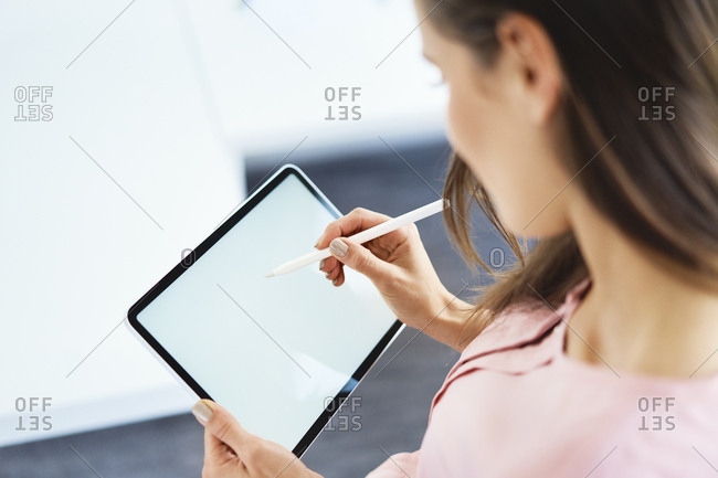 Over the shoulder view of woman drawing on tablet using pencil