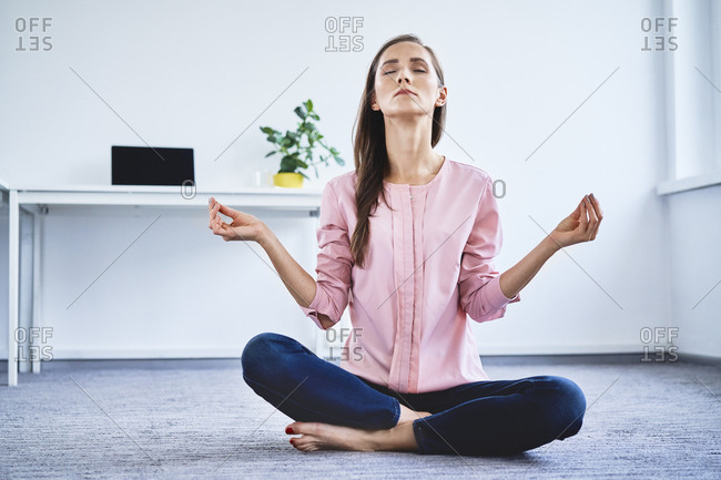 Young woman meditating on floor in office