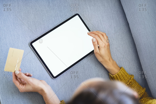 Overhead view of woman using tablet and credit card to buy online from home