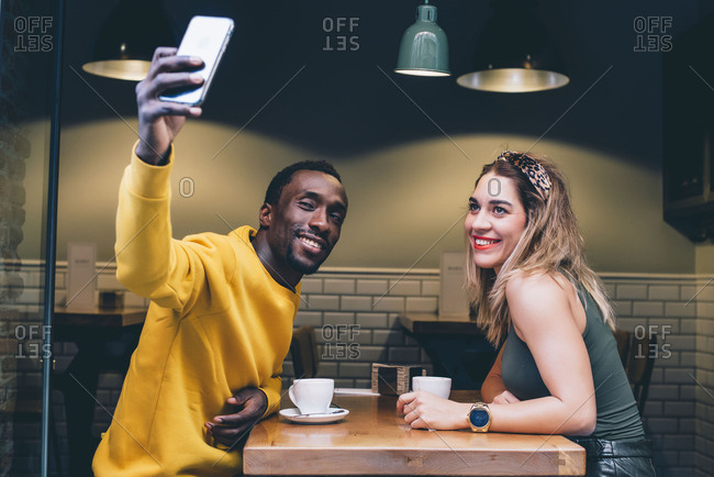 Portrait of smiling couple in a coffee shop taking selfie with smartphone