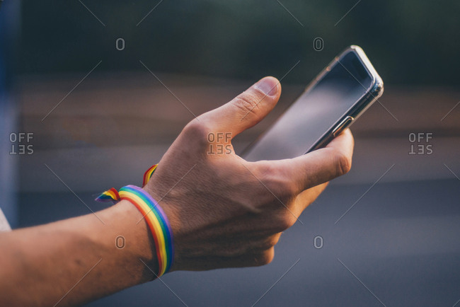 Hands of man with pusera gay flag holding an smartphone