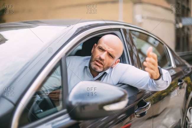 Businessman driving car and looking angry