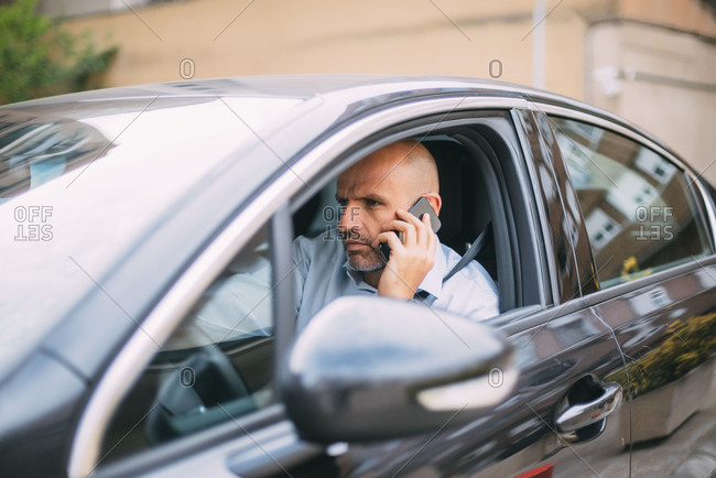 Businessman driving vehicle and using smartphone